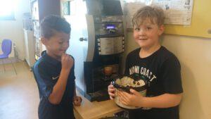 leerlingen zamelen koffieprut in bij het koffiezet apparaat in de docentenkamer om daar oesterzwammen op te kweken